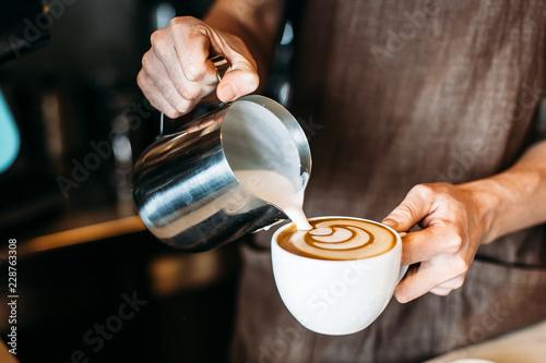 Foto Barista pouring latte foam over coffee, espresso and creating a perfect latte ar
