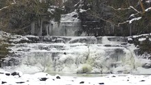 Frozen Waterfall With Snow Falling At Cotter Force In The Yorkshire Dales National Park