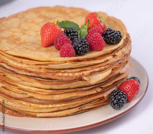 Стопка блинов на тарелке с фруктами