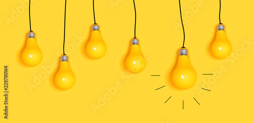 Fotografía  Many hanging light bulbs on a yellow background