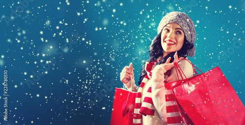 Happy young woman holding shopping bags in a snowy night Tablou Canvas