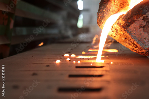 Fototapeta Casting iron by green sand process ; technology for Casting, in the metal industry, the process that molten metal is poured  into a mold , where it solidifies into shape , Industrial background obraz