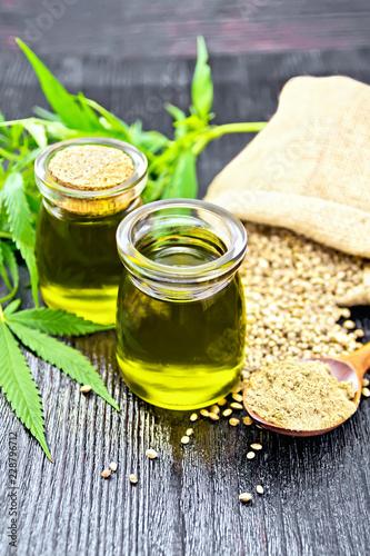 In de dag Kruiderij Oil hemp in two jars and flour in spoon on dark board