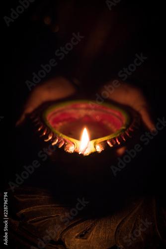 Closeup of Diwali Diya in hand, lady holding glowing clay lamp. Selective focus