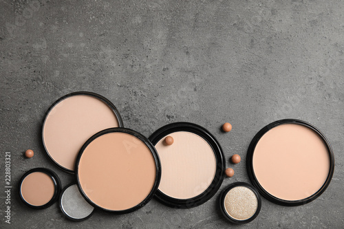 Flat lay composition with various makeup face powders on gray background. Space for text