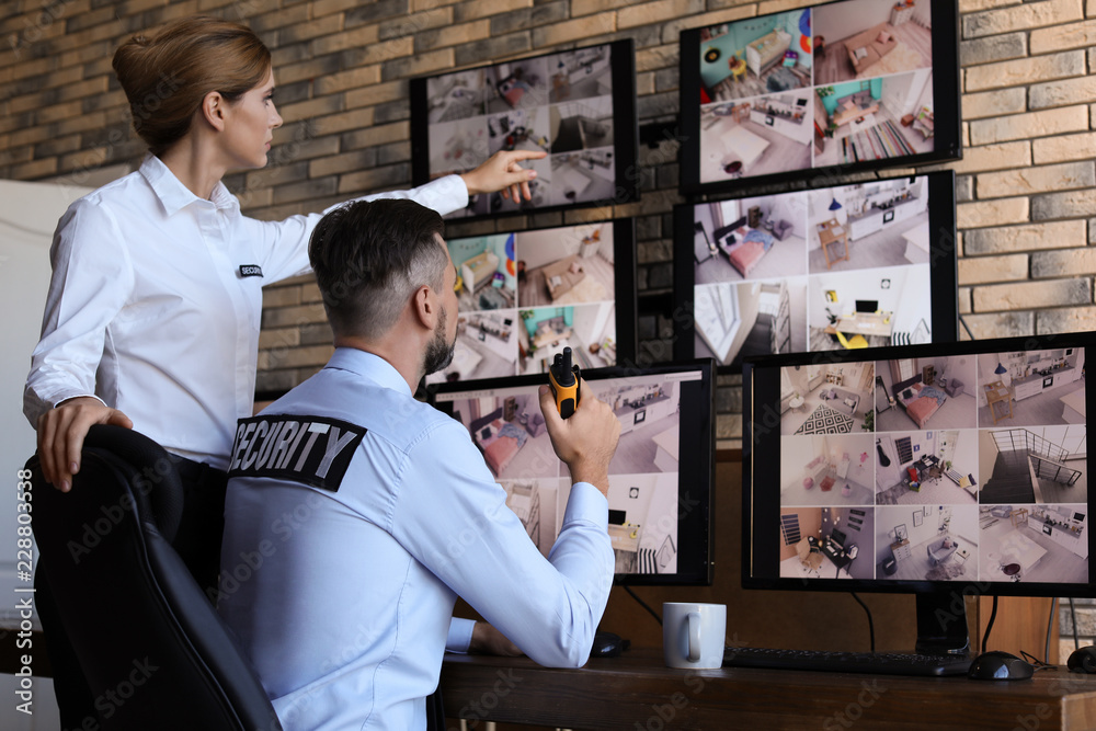 Fototapeta Security guards monitoring modern CCTV cameras indoors