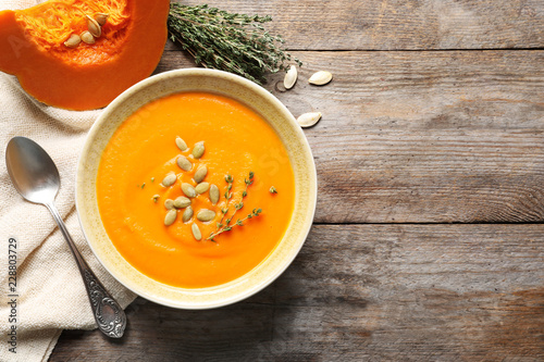 Flat lay composition with bowl of pumpkin soup and space for text on wooden background