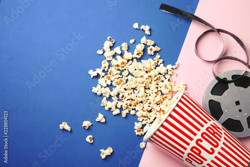 Tasty popcorn and film reel on color background, top view with space for text Fototapet