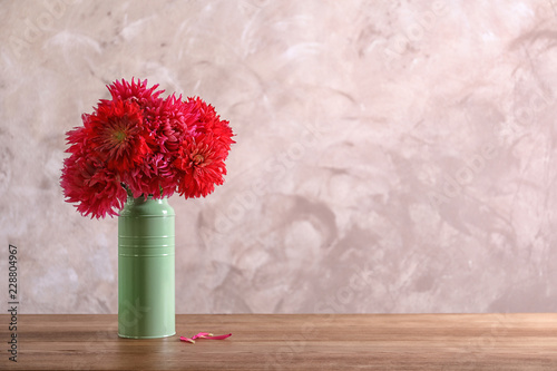 Beautiful dahlia flowers in vase on table against color background. Space for text