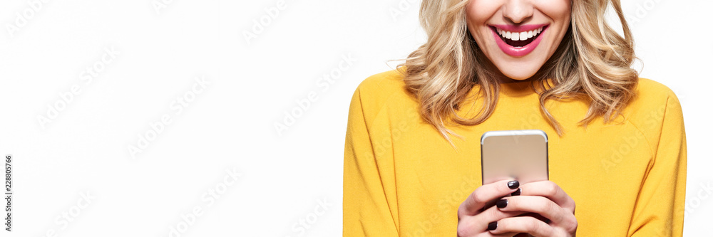 Fototapety, obrazy: Excited young woman looking at her mobile phone smiling. Woman reading text message on her phone, isolated over white background.