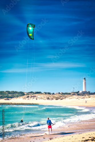 Girl doing kiteboarding under the rays of the sun on the beach of Los Caños de Meca, next to the lighthouse of Trafalgar, on the coast of Cadiz, southern Spain
