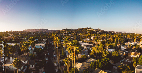 Beverly Hills street with palm trees at sunset in Los Angeles with Hollywood sign on the horizon Fototapeta