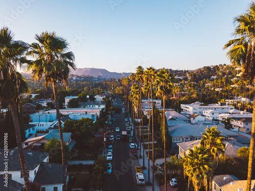 Fotografía Beverly Hills street with palm trees at sunset in Los Angeles with Hollywood sign on the horizon