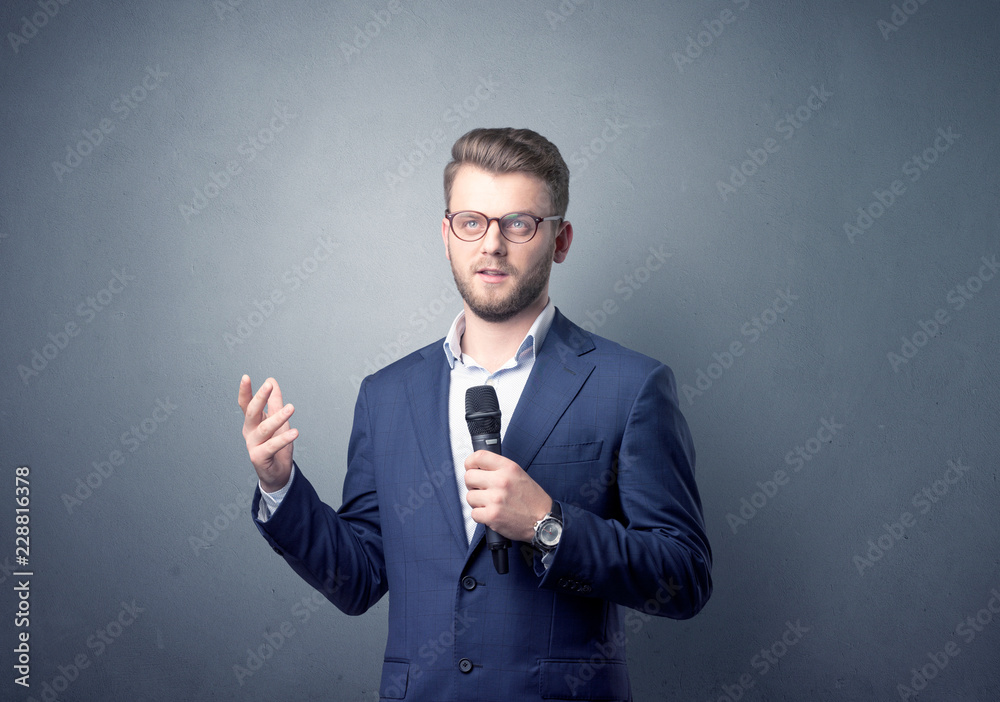 Fototapeta Businessman speaking into microphone with blue background