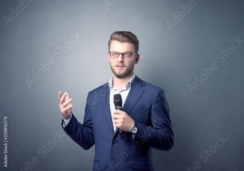 Obraz Businessman speaking into microphone with blue background - fototapety do salonu