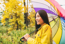 Asian Woman Under Colorful Umbrella On Rainy Day Of Autumn, Rain Fall Fashion Lifestyle Girl Walking In Forest With Yellow Leaves.