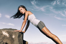Strength Training Fitness Woman Working Out Core With Angled Push Up Exercise On Rock. Asian Athlete Exercising With Body Weight Exercises For Toned Body. Workout In Summer Desert Landscape.
