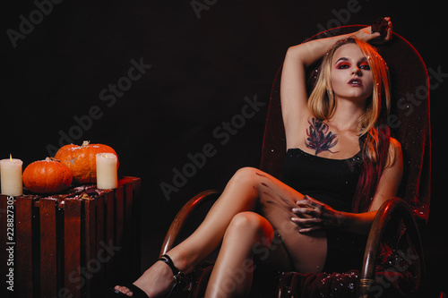 Halloween concept, girl vampire with red eyes red lips sit on rocking chair with pumpkins around Fototapete