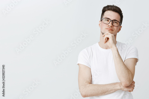 Waist-up shot of creative male photographer looking at model thoughtful holding hand on chin as thinkings making decision standing focused and serious standing against gray background determined