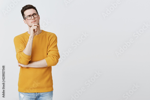 Hmm what if. Smart and thoughtful good-looking guy in geek glasses and cozy yellow sweater holding hand on chin, frowning and looking at upper right corner as thinking, making decision or assumption
