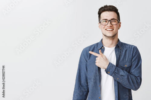 Polite and friendly handsome young caucasian man in glasses and blue shirt over t-shirt smiling joyfully as pointing left at copy space showing cool place for advertisement over grey wall