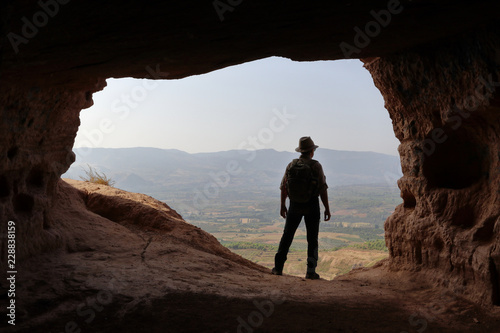 ISOLATED MAN WITH BACKPACK AND HAT AT THE ENTRANCE OF A CAVE Canvas Print