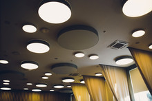 Big Grey Ivory Hexagons With Light Inside Is On Ceiling With Classic Office Squares In Modern Design Studio, Large Hexagon Chandelier Against Geometric Ceiling As A Decor Modern Element.