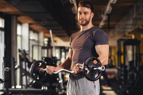 Fotografia  Handsome man doing biceps lifting in a gym