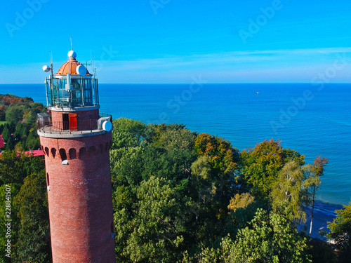 Fototapeten Leuchtturm Aerial view at red lighthouse, at baltic sea coast with forest and buildings.