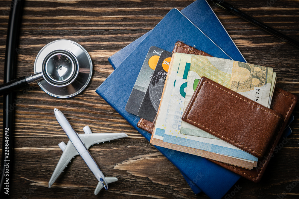 Fototapeta Medical tourism concept - passports, stethoscope, airplane, money top view