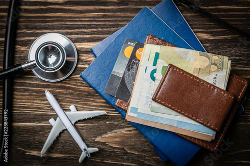 Fotografia  Medical tourism concept - passports, stethoscope, airplane, money top view