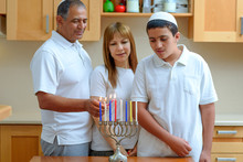 Happy Multiracial Jewish Family Is Lighting Candles For The Jewish Holiday Hanukkah. Jewish Dad, Mom And Teenager Son Or Grandparents With Grandson Lighting Chanukkah Candles In A Menorah For Holidays