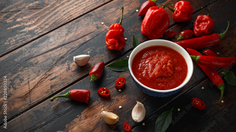 Fototapeta spicy hot sweet chili sauce with mix of chilli pepper, garlic and tomatoes on rustic wooden background