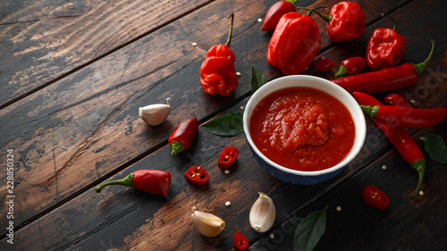 Tuinposter Hot chili peppers spicy hot sweet chili sauce with mix of chilli pepper, garlic and tomatoes on rustic wooden background