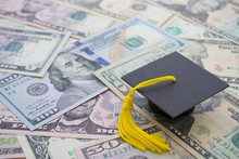 Graduation Cap University Or College Degree On US Dollars Banknotes Background. Education Expense Budget Plan Of Money Saving, Loan, Debt, Personal Loan, Scholarship For Studying Abroad Concept.