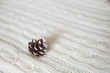 Christmas composition.Pine cone on a knitted white plaid. Copy space.