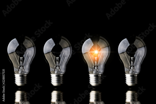 Photo  creativity startup business ideas concept with glow light bulb on black backgrou