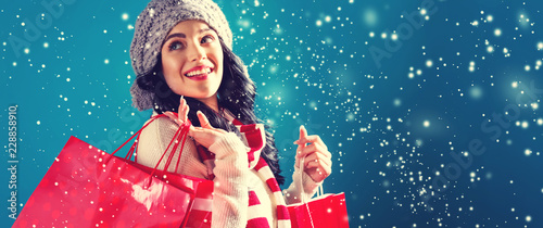 Fototapeta Happy young woman holding shopping bags in a snowy night obraz