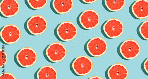 Fotografie, Obraz Halved fresh grapefruits on bright color background