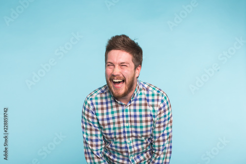 Leinwand Poster Emotion, people and fun concept - Young handsome man laughing on blue background
