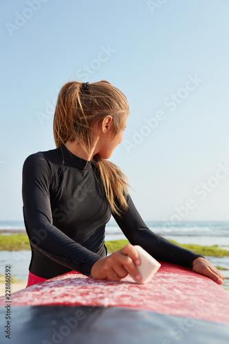 Photo  Sporty woman with pony tail, dressed in swimingsuit, prepares for surf trip, wax
