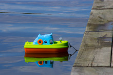 A Toy Boat Moored In Water To A Wooden Bridge
