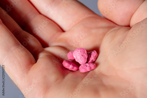 Foto Red Army Skull, Ecstasy, pain killer or xtc pills in the palm of a caucasian hand