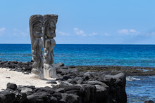 Two Wooden Tikis In The Place Of Refuge (Honaunau) Sanctuary, On The Big Island Of Hawaii. Standing In White Sand With A Black Lava Barrier Wall; Pacific Ocean And Blue Sky Are In The Background.