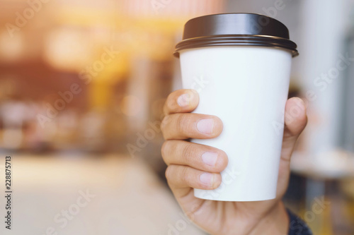 Photo sur Toile Cafe young man hand holding Paper cup of take away drinking coffee hot on cafe coffee shop.