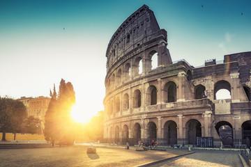 Koloseum w Rzymie, Włochy, o wschodzie słońca. Kolorowe tło podróży.
