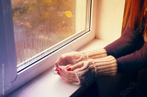 Foto op Aluminium Thee Women's hands in red fingerless gloves hold a cup of hot tea. Woman looks out the window behind which it is raining