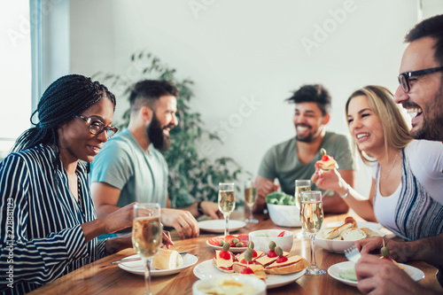Group Of Happy Young Friends Enjoying Dinner At Home Canvas Print