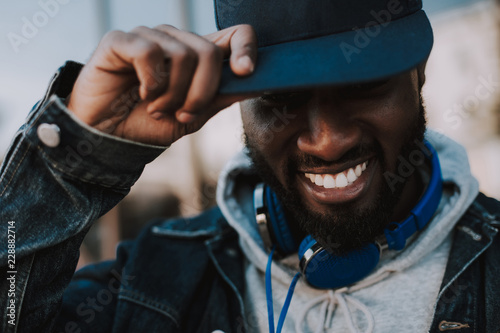 Close up of a positive stylish afro american man smiling while wearing his trendy cap - 228882714