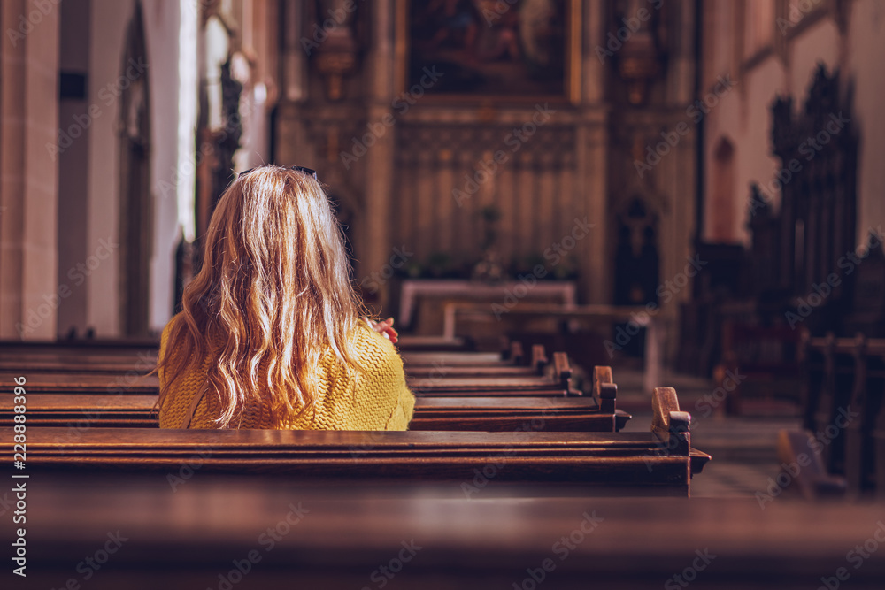 Fototapeta Young woman praying and meditating in church.